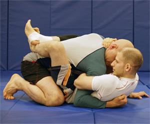 Cel de jos rupe postura celui de deasupra folosindu-se de overhook (mana stanga a celui de jos) si de controlul pe cap (mana dreapta). Astfel, nu poate fi lovit si este mult mai putin expus la procedee.